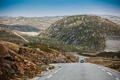 Die kurvenreiche Straße zwischen den felsigen Bergen in Norwegen Stockfotos