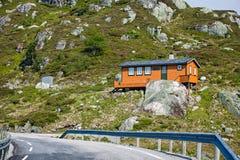 Die kurvenreiche Straße zwischen den felsigen Bergen in Norwegen Rotes hous Stockbild