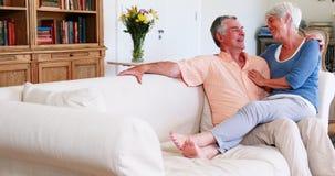Die lächelnde ältere Frau, die an sitzt, bemannt Schoss im Wohnzimmer stock footage