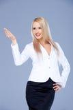 Lächelnde blonde Geschäftsfrau, die auf Kopienraum zeigt Stockfotografie