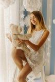 Die lächelnde blonde Jugendliche hält den Teddybären beim Sitzen auf dem Stuhl Lizenzfreie Stockbilder