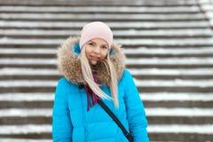 Die lächelnde entzückende blonde Frau der Junge, die den blauen mit Kapuze Mantel schlendert in Stadt des verschneiten Winters tr Stockfoto
