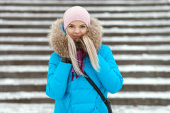 Die lächelnde entzückende blonde Frau der Junge, die den blauen mit Kapuze Mantel schlendert in Stadt des verschneiten Winters tr Stockfotografie