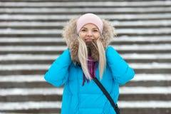 Die lächelnde entzückende blonde Frau der Junge, die den blauen mit Kapuze Mantel schlendert in Stadt des verschneiten Winters tr Lizenzfreies Stockfoto
