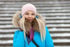 Die lächelnde entzückende blonde Frau der Junge, die den blauen mit Kapuze Mantel schlendert in Stadt des verschneiten Winters tr Stockbild