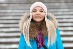 Die lächelnde entzückende blonde Frau der Junge, die den blauen mit Kapuze Mantel schlendert in Stadt des verschneiten Winters tr Stockfotos