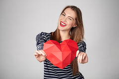 Die lächelnde Frau, die rotes polygonales Papierherz hält, formen Stockbilder