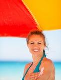 Die lächelnde Frau, die Sonne aufträgt, blocken Creme auf Arm Lizenzfreie Stockbilder