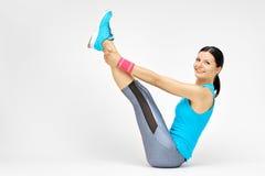 Die lächelnde Frau, die tut, pilates ausdehnend, trainiert an der Turnhalle Stockfotos