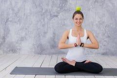 Die lächelnde Frau, die Yoga tut, werfen das Halten des Apfels auf ihrem Kopf auf Lizenzfreie Stockbilder