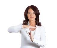 Die lächelnde Frau, die Zeit heraus zeigt, gestikulieren Lizenzfreies Stockbild