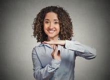 Die lächelnde Frau, die Zeit heraus zeigt, gestikulieren mit den Händen Lizenzfreies Stockfoto
