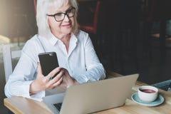 Die lächelnde Geschäftsfrau, die im weißen Hemd gekleidet wird, sitzt bei Tisch Lizenzfreie Stockbilder
