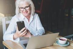 Die lächelnde Geschäftsfrau, die im weißen Hemd gekleidet wird, sitzt bei Tisch Lizenzfreie Stockfotografie