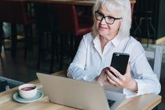 Die lächelnde Geschäftsfrau, die im weißen Hemd gekleidet wird, sitzt bei Tisch Stockbild