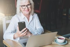 Die lächelnde Geschäftsfrau, die im weißen Hemd gekleidet wird, sitzt bei Tisch Lizenzfreie Stockfotos