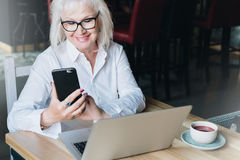 Die lächelnde Geschäftsfrau, die im weißen Hemd gekleidet wird, sitzt bei Tisch vor Laptop und der Anwendung von Smartphone freib Lizenzfreie Stockfotografie