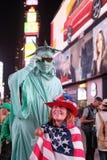 Die lächelnde gesehene Frau drapierte in einer US-Flagge und IN US-Hut lizenzfreie stockfotografie