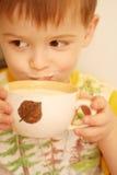 Die lächelnde Getränkmilch des Kindes Stockfoto