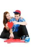 Die lächelnde Jugendliche und Junge, die einen Valentinsgruß anhalten, schnitten vom roten Papier mit Scheren heraus Lizenzfreies Stockfoto
