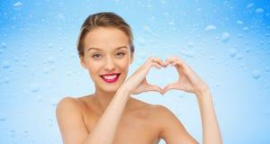 Die lächelnde junge Frau, die Herz zeigt, formen Handzeichen Lizenzfreies Stockfoto