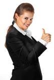 Die lächelnde moderne Geschäftsfrau, die Daumen zeigt, up GE Lizenzfreies Stockbild
