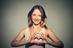 Die lächelnde nette glückliche junge Frau, die Herz macht, unterzeichnen mit den Händen Stockfoto