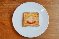 Die lächelnden Gesichter gemalt auf dem Scheibenbrot, glückliches Frühstück Konzept stockfotos