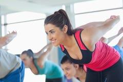 Die lächelnden Leute, die Machteignung tun, trainieren an der Yogaklasse Stockfoto