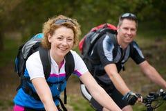 Die lächelnden Paare, die ein Fahrrad genießen, reiten draußen Stockbild