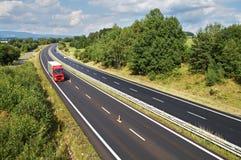 Die ländliche Landschaft mit einer Landstraße zeichnete mit Bäumen, rotem LKW und Autos auf der Straße lizenzfreie stockfotografie
