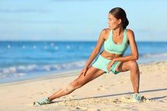 Die Läuferfrau, die Beine mit dem Laufleinenkniesehnenausdehnungs-Übungsbein ausdehnt, dehnt aus Stockfoto