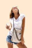 Die lachende Frau der Mode, die stilvollen Blick trägt, trinkt Soda und wirft auf Farbhintergrund auf Stockfotografie