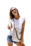 Die lachende Frau der Mode, die stilvollen Blick trägt, trinkt Soda und wirft auf lokalisiertem Hintergrund auf Lizenzfreie Stockfotos