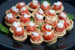 Die Lachsrollen, die mit Käse angefüllt wurden, besprühten Samen des indischen Sesams Stockfotos