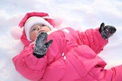 Die Lagen des kleinen Mädchens auf einem Schnee Stockbild