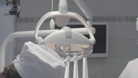 Die Lampe im Operationsraum Zahnchirurgie Die Krankenschwester unterstützt den Doktor, die nicht Farbe, die korrigiert wird, gut  stock footage