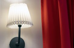 Die Lampe mit gewölbtem Lampenschirm auf der Wand mit einem roten Vorhang lizenzfreie stockbilder