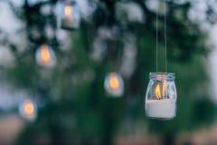 Die Lampe, die von einem Glas mit einer Kerze hergestellt wird, hängt an einem Baum nachts Hochzeitsnachtdekor lizenzfreie stockfotos