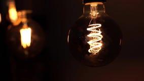 Die Lampen leuchtet in der Dunkelheit Wolframglühlampelampen über schwarzem Hintergrund Konzept von hellem und von Dunklem, Idee stock footage