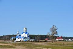 Die Landschaft der weißen Kirche steht voll am Rand des Dorfs im Frühjahr stockfotos