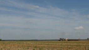 Die Landwirtschaft, ein Traktor erntet auf dem Bauernhoffeld nahe der Ranch stock footage