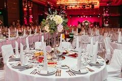 Die lange festliche Tabelle diente Teller und verziert mit Niederlassungen des Grüns Wedding Bankett Lizenzfreie Stockbilder