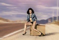 Die langen Beine der Frau, die auf Gepäckkoffer sitzen, verlassen Stockfotografie