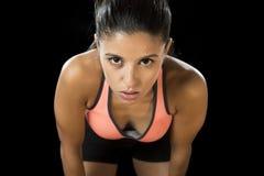 Die lateinische Sportfrau, die in heftigem aufwerfen und die badass stellen Ausdruck mit dünnem Körper des Sitzes gegenüber lizenzfreie stockbilder