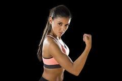 Die lateinische Sportfrau, die in heftigem aufwerfen und die badass stellen Ausdruck mit dünnem Körper des Sitzes gegenüber Stockbild