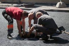 Die laufende Asphaltierung, Arbeitskräfte installieren Abwasserkanaleinsteigeloch Lizenzfreie Stockfotos