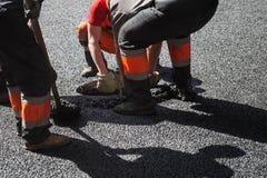 Die laufende Asphaltierung, Arbeitskräfte installieren Einsteigeloch Lizenzfreie Stockbilder