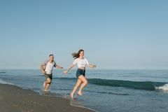 Die laufenden Paare auf der Seeküste Stockfoto