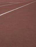 Die laufenden Weisen am Stadion mit künstlicher Beschichtung des Gummis Stockfoto